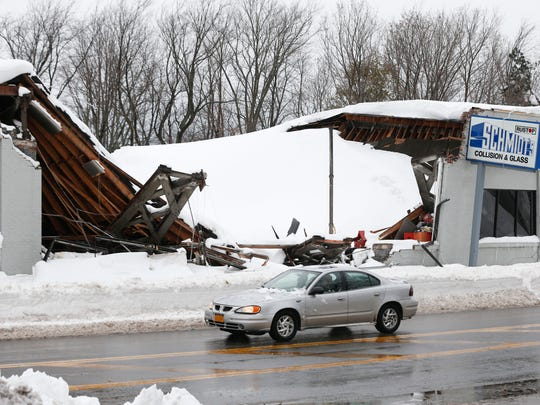 A car drives by Schmidt's Collision and Glass after the roof collapsed after taking on heavy snow during this week's lake-effect snowstorms on Saturday, Nov. 22, 2014, in Hamburg, N.Y.