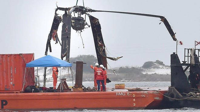 Crews lower a piece of a Black Hawk helicopter onto a barge in the Santa Rosa Sound near Pensacola, Florida, on March 13. Seven Marines and four Louisiana National Guardsmen, including David Strother of Alexandria, were killed in the crash.