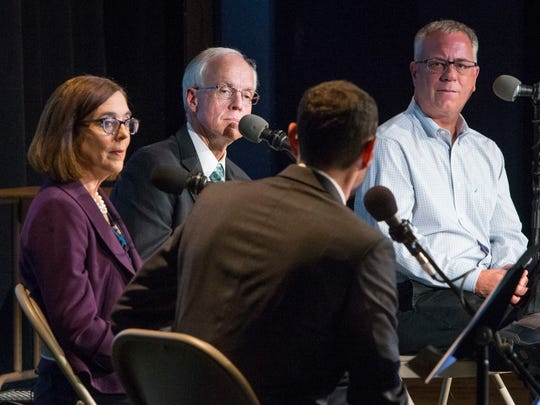 Oregon Gov. Kate Brown, Republican candidate Bud Pierce and Independent Party of Oregon candidate Cliff Thomason look toward debate moderator Dave Miller of Oregon Public Broadcasting during the gubernatorial debate at Churchill High School in Eugene in a previous gubernatorial debate.
