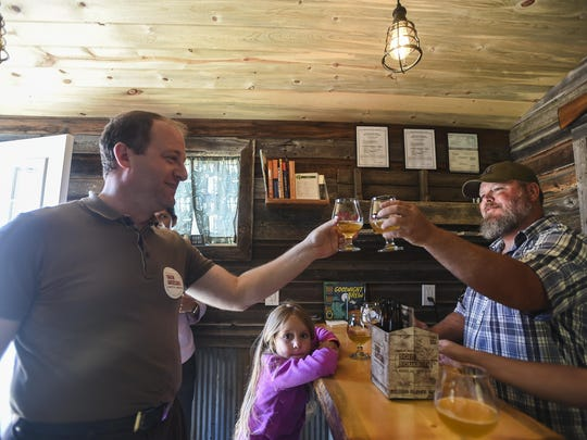 U.S. Rep. Jared Polis, left, raises a glass of beer with Aaron Gray, co-founder of Soul Squared Brewing.