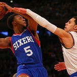 Philadelphia 76ers guard Ish Smith (5) takes a shot defended by New York Knicks guard Shane Larkin (0) during the first half on Sunday at Madison Square Garden.