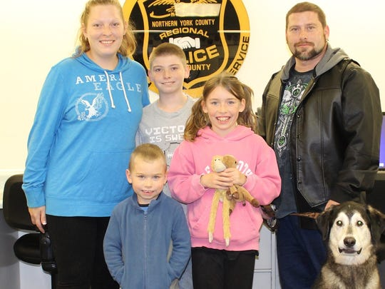Tim Luckenbaugh, right, fiancee Natasha Brenner Luckenbaugh, his three children, ages 12, 10 and 5, and Diesel pose for a picture after Diesel was honored by Northern Regional Police on Tuesday.