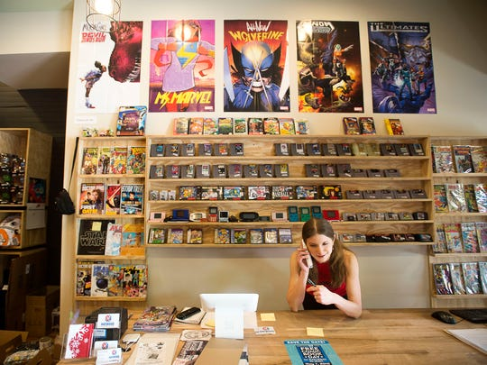 Sales assistant Morgan Albritton answers the phone to speak to a customer April 27 at Haywood Comics in West Asheville.