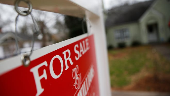"""This Jan. 26, 2016 file photo shows a """"For Sale"""" sign hanging in front of an existing home in Atlanta."""