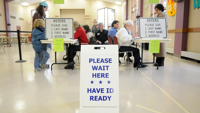 People register to vote at First United Presbyterian Church in De Pere. Voter ID rules will be in effect for elections this year.