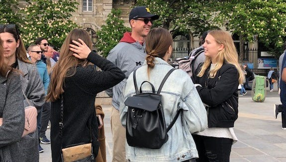 Jim Harbaugh chats with some Michigan students studying abroad in France on Saturday.