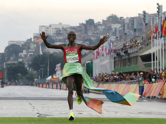 FILE - In this Sunday, Aug. 21, 2016 file photo, Kenya's Eliud Kipchoge crosses the finish line to win the men's marathon at the 2016 Summer Olympics in Rio de Janeiro, Brazil. Kenya had its most successful Olympics ever this year, but a government-ordered report seen Tuesday, Nov. 29, 2016 by The Associated Press has revealed how utterly chaotic the Kenya Olympic team's preparation and management was. (AP Photo/Petr David Josek, File)