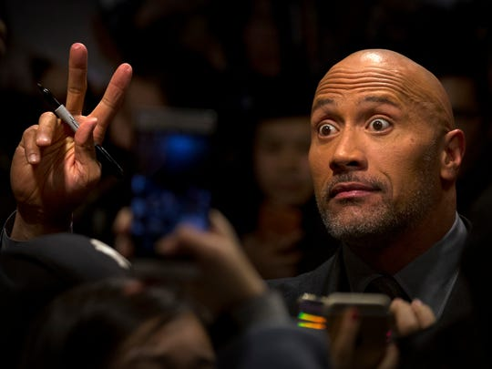 Dwayne Johnson gestures to fans before a press conference for the movie 'Jumanji: Welcome to the Jungle' in Beijing, Thursday. The hit movie opens in China on Jan. 12.