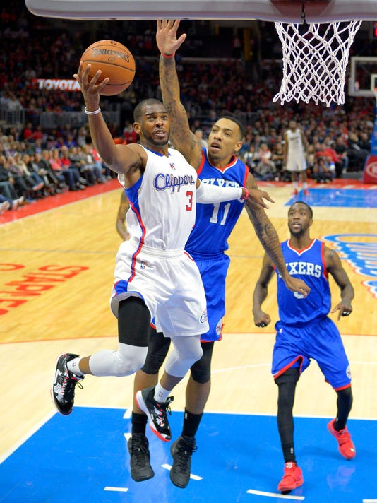 Los Angeles Clippers guard Chris Paul, left, goes up for a shot as Philadelphia 76ers forward Malcolm Thomas, center, defends and guard Tony Wroten looks on during the second half of an NBA basketball game, Saturday, Jan. 3, 2015, in Los Angeles. The Clippers won 127-91. (AP Photo/Mark J. Terrill)