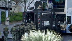 Las Vegas SWAT officers surround a bus along Las Vegas
