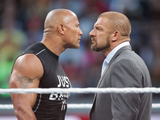 "Dwayne ""The Rock"" Johnson stares off against WWE superstar Triple-H at WrestleMania 31 on Sunday."
