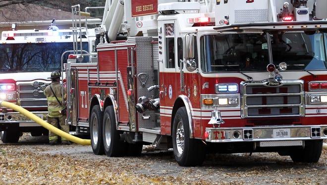 Des Moines fire trucks sit on a city street.
