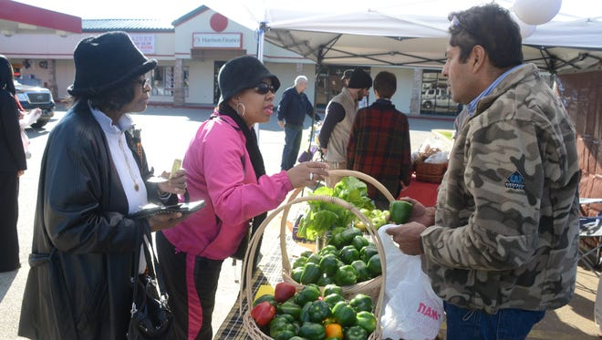 Shirley Deal (left) and daughter Shirley Roque are purchase green peppers Tuesday from Felipe Cazares of Gray Walk Farms at the Mid-Week Farmer's Market held Tuesday on the corner of Texas and Jackson streets in Alexandria. Cooler than normal temperatures didn't detract customers. The markets is held from 3-6 p.m. every Tuesday.