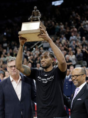 San Antonio Spurs forward Kawhi Leonard holds his NBA defensive player of the year trophy.