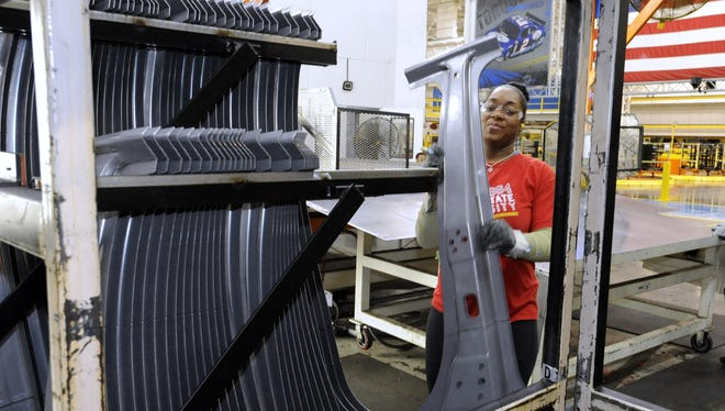 UAW worker Ashley Bailey, of Eastpointe, puts a Durango B-Pillar off a conveyor belt and puts it onto a shipping rack after it is stamped by one of the new presses.