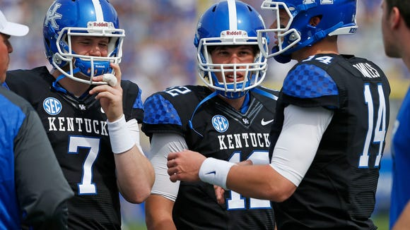 Kentucky Wildcats quarterbacks Drew Barker (7), Reese Phillips (12) and Patrick Towles (14) talked on the sideline during the first half the annual Blue White spring football game at Commonwealth Stadium in Lexington, Ky. April 26, 2014