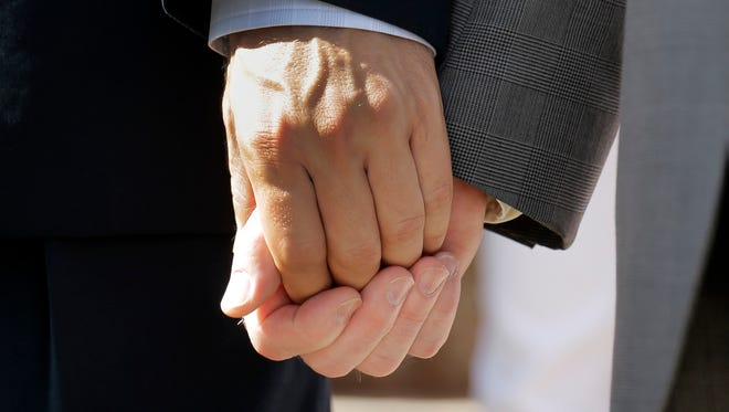 A gay couple holds hands during a news conference celebrating marriage equality in Austin, Texas.