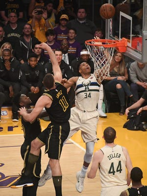 Bucks forward Giannis Antetokounmpo gets past Lakers center Brook Lopez and forward Julius Randle for a shot  in the first quarter Friday night in Los Angeles.