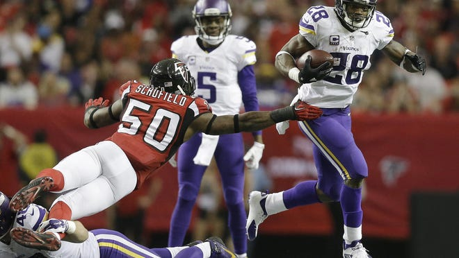 Minnesota Vikings running back Adrian Peterson (28) runs past Atlanta Falcons outside linebacker O'Brien Schofield (50) during the second half of an NFL football game Sunday in Atlanta.