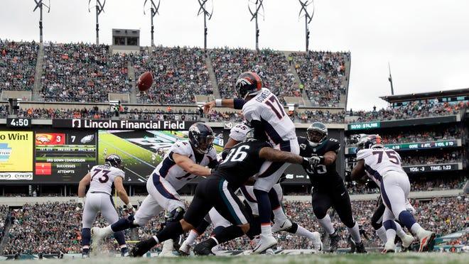 Denver Broncos' Brock Osweiler (17) is hit by Philadelphia Eagles' Derek Barnett (96) during the first half of an NFL football game, Sunday, Nov. 5, 2017, in Philadelphia. (AP Photo/Michael Perez)