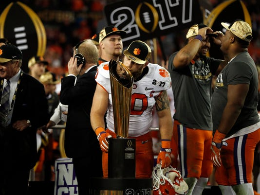Clemson's Ben Boulware kisses the championship trophy after the NCAA college football playoff championship game Tuesday, Jan. 10, 2017, in Tampa, Fla. Clemson won 35-31. (AP Photo/John Bazemore)