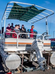 Eli Vigil, left, and Dylan Tafoya-Vigil, right, man the back of the boat at a tailgate party before the NMSU homecoming football game Saturday afternoon outside Aggie Memorial Stadium on Oct. 28, 2017.
