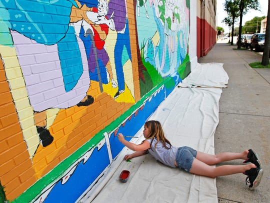 Olivia Ortiz-Simos, 8, works on a new community mural.
