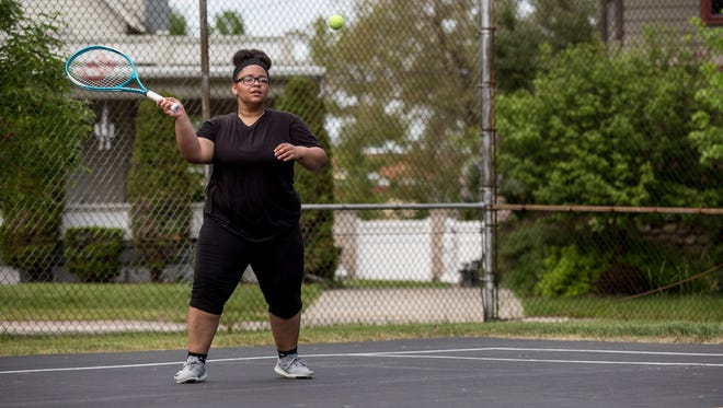Maleena Stewart, 15, takes a swing while playing tennis with friends Friday, May 27, 2016 at Lincoln Park in Port Huron.