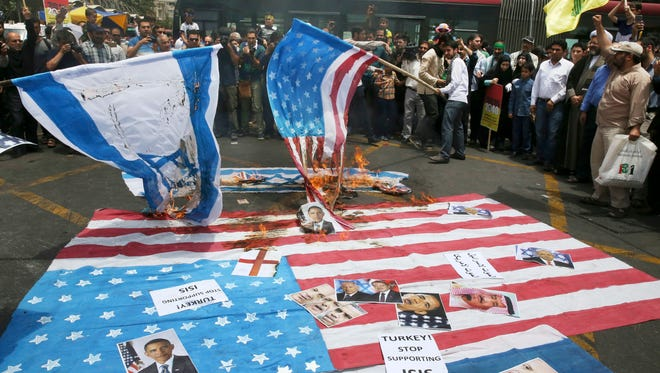 Iranian demonstrators burn representations of U.S. and Israeli flags with portraits of President Obama, Israeli Prime Minister Benjamin Netanyahu, Turkish President Recep Tayyip Erdogan and Saudi Arabia's King Salman on the ground in their annual pro-Palestinian rally marking Al-Quds (Jerusalem) Day in Tehran, Iran, on July 1, 2016.