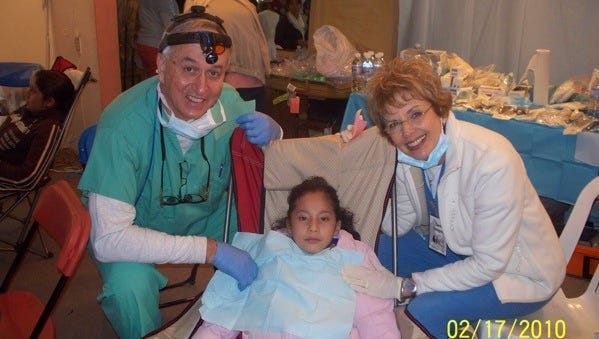 Don and Carol Spurgeon pose with a young patient at one of the dental clinics they have set up through their volunteer work with HealthCare Ministries.