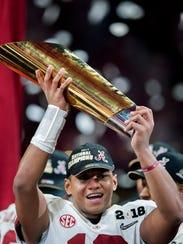 Alabama quarterback Tua Tagovailoa (13) lifts the National
