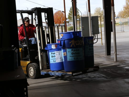 Food barrels are moved into ECHO Food Bank Wednesday, Nov. 15, 2017, in Farmington.