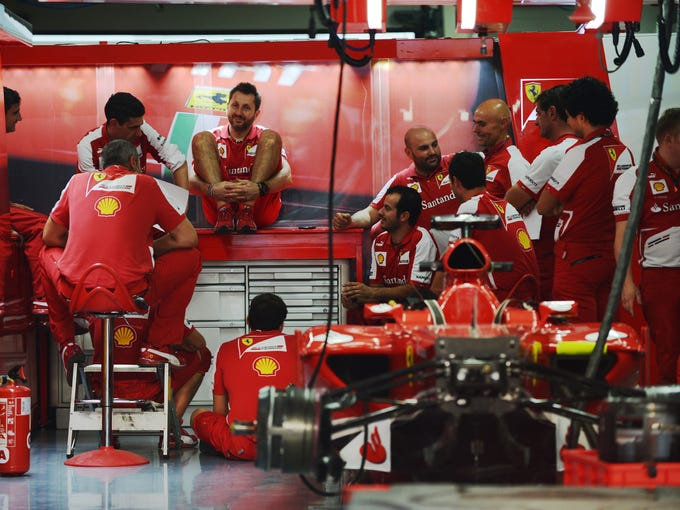 Pit crew members of the Ferrari team attend a crew meeting at the garage at The Buddh International circuit in Greater Noida on the outskirts of New Delhi on October 24, 2013, ahead of the Formula One Indian Grand Prix 2013. The Formula One Indian Grand Prix 2013 takes place on October 27.  AFP PHOTO/Roberto SCHMIDT        (Photo credit should read ROBERTO SCHMIDT/AFP/Getty Images)
