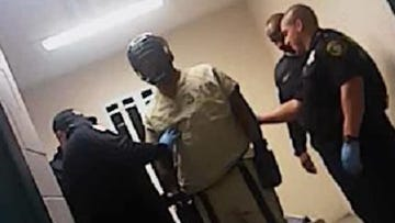 Officers outfit an inmate with a hockey mask and thick gloves to keep him from gouging out his eye.