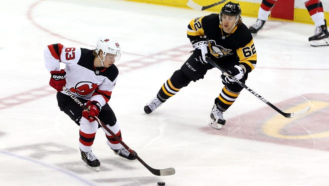 New Jersey Devils left wing Jesper Bratt (63) skates with the puck against Pittsburgh Penguins left wing Carl Hagelin (62) during the second period at PPG PAINTS Arena.