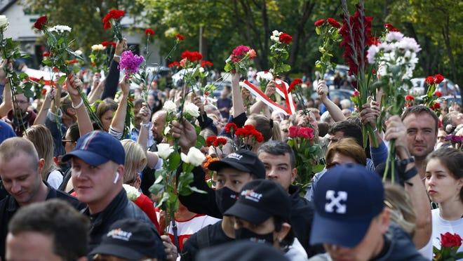 People wave flowers at the farewell hall during the funeral of Alexander Taraikovsky who died amid clashes protesting the election results, in Minsk, Belarus, Saturday.