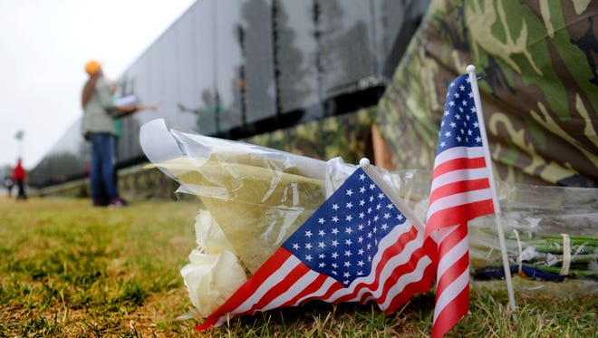 """Flowers with flags are placed at """"The Moving Wall"""" at the Ventura County Government Center. The wall is a half-size replica of the Vietnam Veterans Memorial in Washington, D.C."""