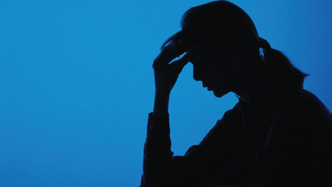 Silhouette of woman holding her head