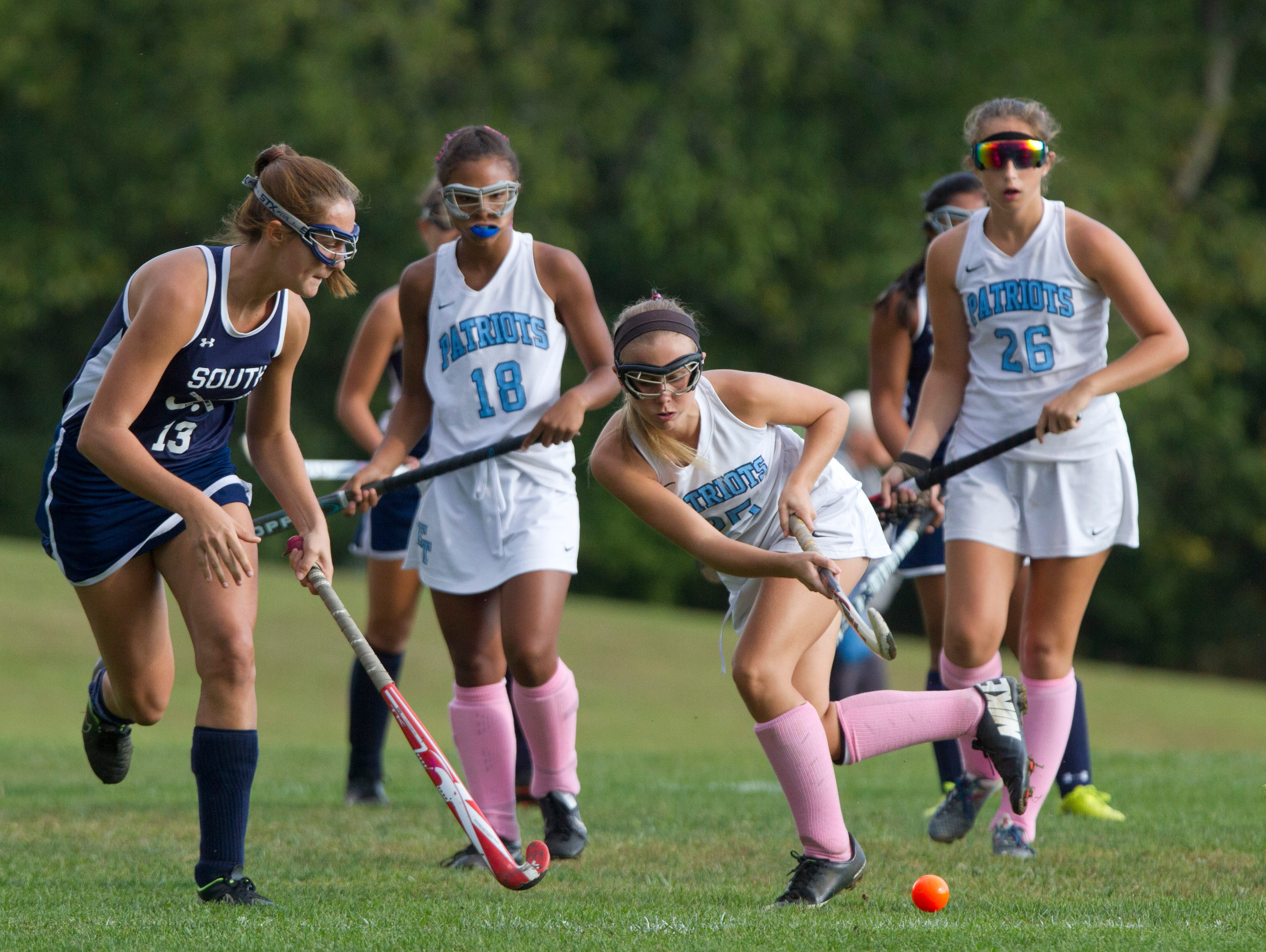 Freehold Township's Jessica Applegate advances the ball down the field during first half action as she's guarded by Middletown South's Julia Valkos. Middletown South Field Hockey vs Freehold Twp in Freehold, NJ on October 8, 2015