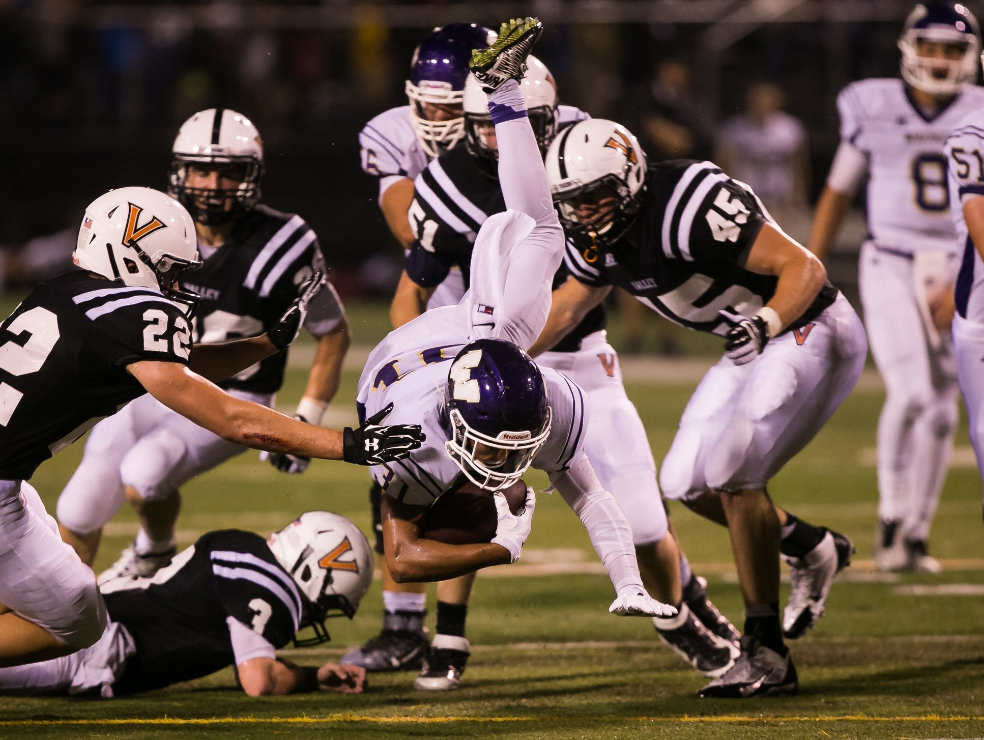 Waukee's Daniel Ray gets up-ended during their game against Valley High School at Valley's football field in West Des Moines on Friday, August 28, 2015.