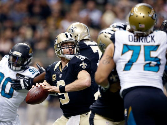 New Orleans Saints quarterback Drew Brees (9) passes under pressure from Jacksonville Jaguars defensive end Jared Odrick (75) in the first half of an NFL football game in New Orleans, Sunday, Dec. 27, 2015. (AP Photo/Jonathan Bachman)