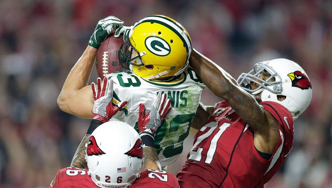 Green Bay Packers receiver Jeff Janis (83) catches a Hail Mary against Arizona Cardinals cornerback Patrick Peterson (21) and Rashad Johnson (26) at the end of the fourth quarter during their NFC divisional playoff game at University of Phoenix Stadium.