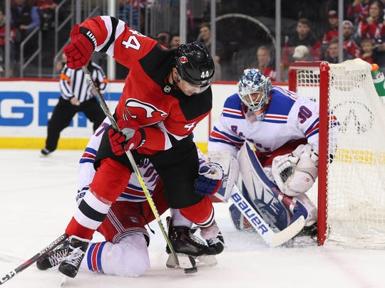 New Jersey Devils left wing Miles Wood (44) passes the puck between his legs in front of the net of New York Rangers goalie Henrik Lundqvist (30) during the second period at Prudential Center on Thursday, Dec. 21, 2017.