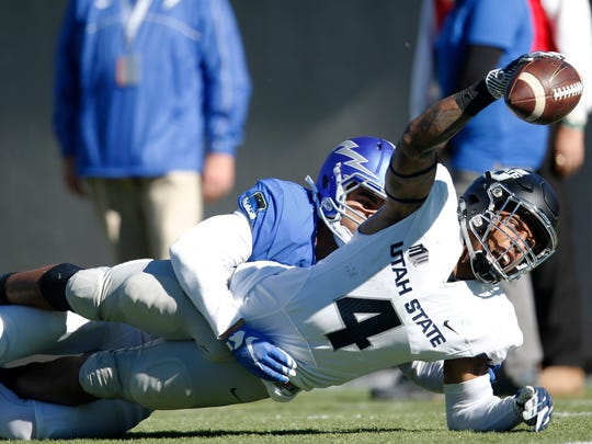 Utah State wide receiver Hunter Sharp, front, dives into the end zone for a touchdown after catching a pass in front of Air Force defensive back Jesse Washington in the first half of an NCAA college football game Saturday, Nov. 14, 2015, at Air Force Academy, Colo