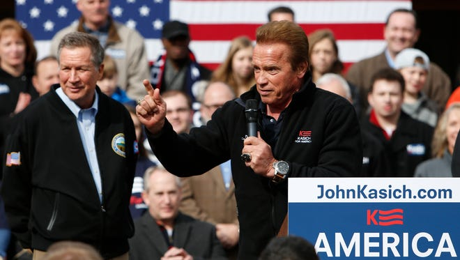 Former California Gov. Arnold Schwarzenegger, right, introduces Republican presidential candidate, Ohio Gov. John Kasich, during a campaign rally Sunday, March 6, 2016, in Columbus, Ohio. Schwarzenegger is throwing his support to Kasich in the presidential contest.  (AP Photo/Jay LaPrete)