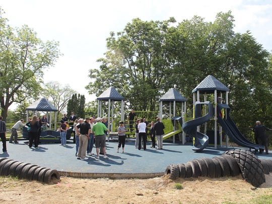 """Clients and friends enjoy Arc of Southeast Iowa's new playground on Tuesday, June 2, 2015. The playground is disability-friendly and includes a wheelchair-accessible """"Sway Fun Glider."""""""