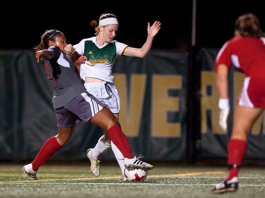 University of Vermont forward Aly Spencer, center, charges in on goal against Sacred Heart during Friday night's women's soccer game at Virtue Field.