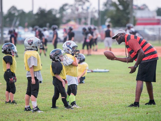 Football teams practice in the baseball outfields at the Navarre Youth Sports Association in Navarre on Wednesday, October 11, 2017.