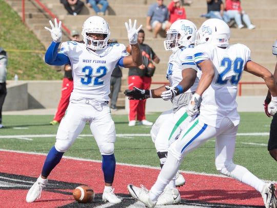 Anthony Johnson (32) and teammates celebrate after a touchdown to tie up the score 7-7 during the UWF vs West Alabama playoff football game in Livingston, Alabama on Saturday, December 2, 2017.