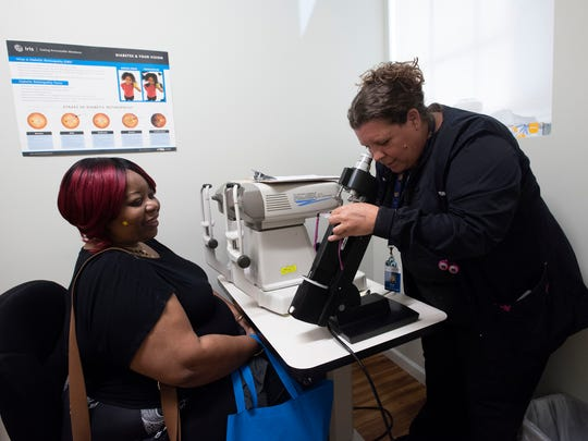 Ophthalmology tech, Wendi Adams, right, gives patient, Tamala Allen a through vision check at the new Escambia Community Clinic building on Jackson Street, Thursday, April 5, 2018.